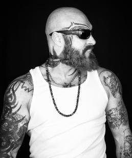 Portræt i sort og hvid af mand med tatoveringer, skæg og solbriller. Men with Attitude af Vibeke Johansson
