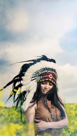 Indianer kvinde i rapsmark med warbonet fjerhovedebeklædning