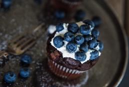 Madfotografering foto af mad. Blåbær muffin med flødeskum