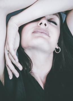 Kvinde med hænderne over hovedet med lukkede øjne portræt