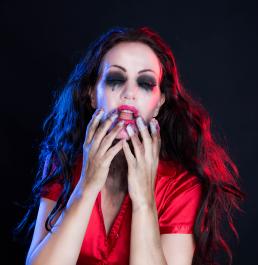 Vampire dark spirit kvinde med makeup plaster på fingeren leg i foto studie og farvet lys