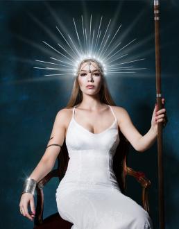 Gudinde med spyd sidder i stol