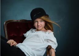 Smuk rødhåret pige med klokkehat i rød Velux stol