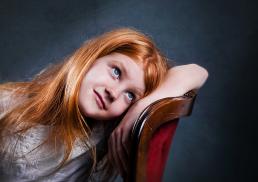 Rødhåret pige portræt som sidder i en stol