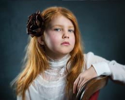 Rødhåret pige med blomst i håret portræt