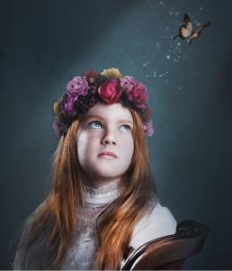 Pige med blomster krans som kigger efter en sommerfugle som flyver væk