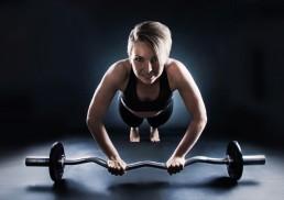 Unge pige med vægtstang træner på gulvet