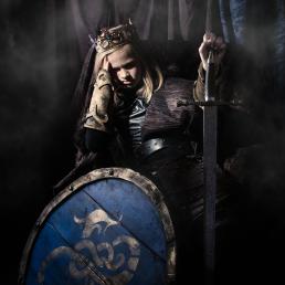 Middelalder prins som sidder på tronen med sit sværd