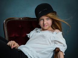 Pige med klokkehat sidder i en stol
