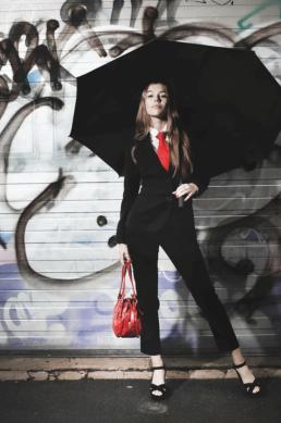 Model fotografering model med stor paraply og rød taske og slips