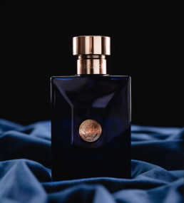 Parfumeflaske i blå på blåt velurstof produktfotografering