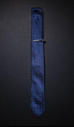 Blåt slips med små blå blomster og slipsenål som produktfoto